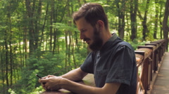 Male texting sms on the cell in the forester Stock Footage