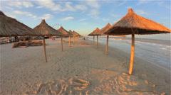 Straw umbrellas on the sea sandy beach. The evening sunset. Empty beds Stock Footage