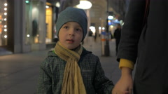Child walking with mother in evening city street Stock Footage