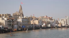 Ghats with Dwarika jagat mandir and pilgrims in Gomti river,Dwarka,India Stock Footage