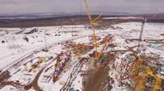 Drone flying over construction area in winter day, yellow cranes and white snow Stock Footage