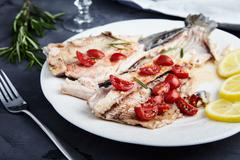 Baked trout with cgerry tomatoes and wine Stock Photos