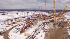 Drone flying back, showing area of stadium construction in winter day with Stock Footage