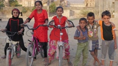 Girls on bicycles and boys at Mahabat Maqbara Mausoleum,Junagadh,India Stock Footage