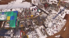 Aerial view of building construction in winter, workers moving, crane is Stock Footage