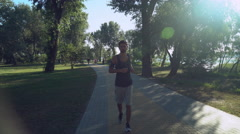 A young guy with headphones running back in the park, where walking and running Stock Footage