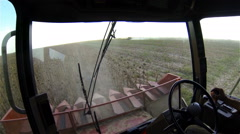 Driver with a cigarette operates a combine harvester during harvesting of Stock Footage