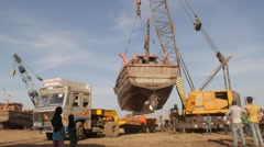 Crane lifting fishery boat,Veraval,India Stock Footage