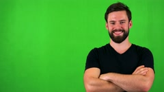 Young handsome bearded man smiles to camera with folded arms - green screen  Stock Footage