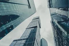 Modern glass silhouettes of skyscrapers in the city Stock Photos