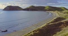 Aerial of man walking on an empty beach in the Coromandel, New Zealand Stock Footage