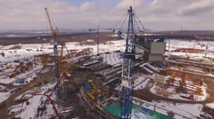 Drone flying close of cabin of huge construction crane on stadium building in Stock Footage