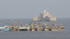 Pier with fishermen boats and Fortim-do-Mar,Diu,India Stock Footage