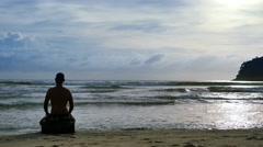 Man practicing meditation on the beach at sunset time Stock Footage