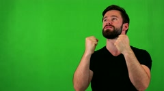 Young handsome bearded man rejoices - green screen - studio Stock Footage