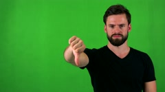 Young handsome bearded man disagree (show thumb down) - green screen - studio Stock Footage