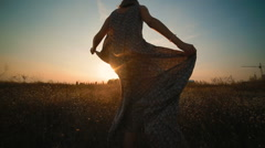A girl in a long, beautiful dress swirls in the field at sunset Stock Footage