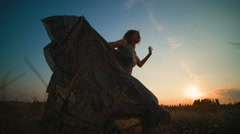 A girl in a long, beautiful dress running across the field at sunset Stock Footage