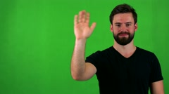 Young handsome bearded man waves with hand - green screen - studio Stock Footage