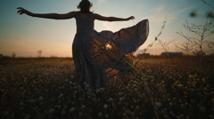 A girl in a long dress is on the field at sunset Stock Footage
