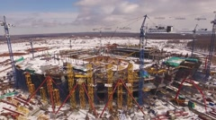 Aerial view of big construction cranes, standing around of stadium building in Stock Footage