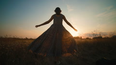 Girl in long beautiful dress running in a field at sunset Stock Footage