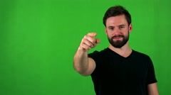Young handsome bearded man points to camera with finger - green screen - studio Stock Footage