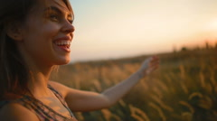 Beautiful , attractive woman smiling broadly in the field at sunset Stock Footage