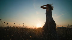 Beautiful young girl spinning in a field at sunset Stock Footage