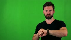 Young handsome bearded man points on watch (show time) - green screen - studio Stock Footage
