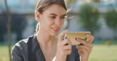 Young , beautiful girl plays games on her smartphone Stock Footage