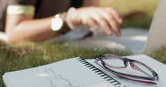 Young female designer working on a laptop in the park lying on the grass Stock Footage