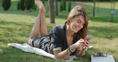 Girl in the park corresponds with friends using smartphone Stock Footage