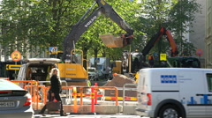 Heavy Equipment working at the construction site. Pedestrians and cars go round. Stock Footage
