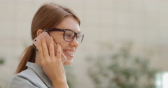 Young and attractive business woman talking on the phone walking along the bank Stock Footage