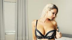 Sexy blonde girl in lingerie in bedroom -  cinematic color grade Stock Footage