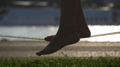 Silhouette of female legs on a slackline rope Stock Footage