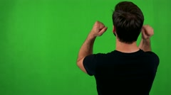 Young bearded man rejoices - shot on back (man looks to screen) - green screen Stock Footage