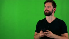 Young bearded man listens music with earphone on smartphone - green screen Stock Footage