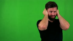 Young handsome bearded man is afraid (man covers his ears) - green sc Stock Footage