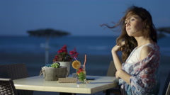 Thoughtful pretty female enjoying cocktail at seaside restaurant, romantic mood Stock Footage