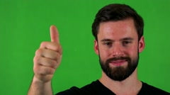 Young handsome bearded man shows thumb up on agreement - green screen - studio  Stock Footage