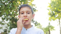 Boy eating potato chips on the street. Teen boy eating junk food Stock Footage