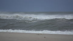 Curling wave crashes on the shore Stock Footage