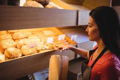 Female baker packing sweet food in bakery shop Kuvituskuvat