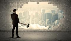 Business man hitting wall with hammer on city view Stock Photos