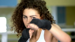 Athletic young curly woman shadow boxing, front view, slow motion Stock Footage