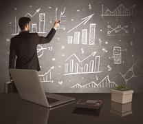 Businessman drawing sales charts on wall Stock Photos