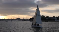 Sail boat sailing into the sunset on cloudy late afternoon harbor race.mp4 Stock Footage