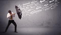Business man standing with umbrella and drawn arrows hitting him Stock Photos